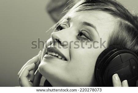 Technology, music and happiness concept - smiling girl teenage in headphones listening music. Black white color, vintage photo
