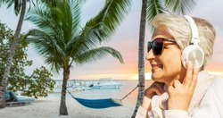 technology, old people and leisure concept - senior woman in headphones and sunglasses listening to music over tropical beach background in french polynesia
