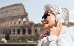 technology, old people and travel concept - senior woman in headphones and sunglasses listening to music over coliseum in rome, italy backgound