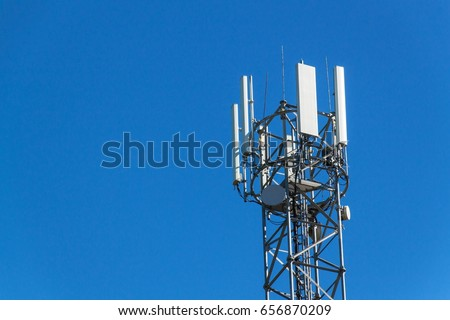 Technology on the top of the telecommunication GSM. Masts for mobile phone signal. Tower with antennas of cellular communication on the background of blue sky.