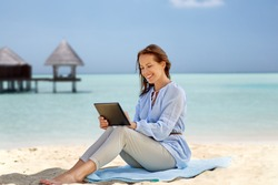 technology, people and leisure concept - happy smiling woman with tablet pc computer over tropical beach and bungalow on maldives background