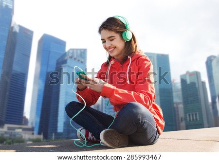 technology,  travel, tourism and people concept - smiling young woman or teenage girl with smartphone and headphones listening to music over singapore city background