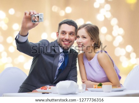 technology, valentines day and people concept - happy couple taking selfie by digital camera at sushi restaurant over festive lights on beige background