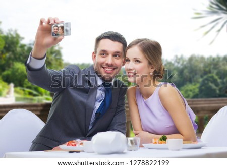 technology, valentines day and people concept - happy couple taking selfie by digital camera at sushi restaurant over summer background