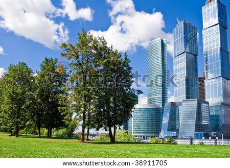 Technology versus nature, modern skyscrapers and green trees
