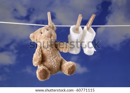 teddy bear and baby booties hanging on a clothes line , background is blue sky with clouds