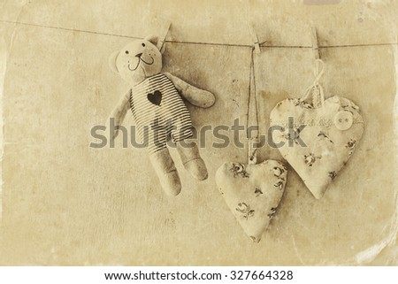 teddy bear and fabric hearts hanging on rope. retro filtered image. old style photo #327664328
