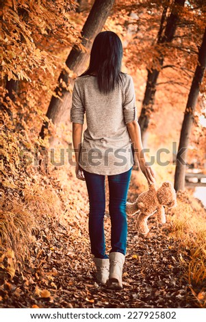 Teddy bear and girl in the woods