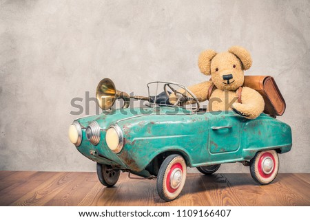 Teddy Bear and old leather school bag driving in rusty retro turquoise toy pedal car with classic brass klaxon in front concrete textured wall background. Vintage style filtered photo #1109166407