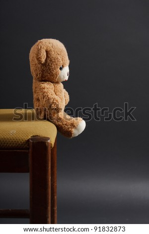 teddy bear at the edge of his chair. loneliness, sadness
