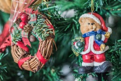 Teddy bear dressed as Santa Claus, wreath of branches and other ornaments on the Christmas tree.