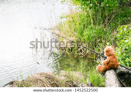 Teddy bear fisherman. Brown teddy bear sits by the lake with a fishing rod and catches fish. Summer nature idyllic landscape #1452522500