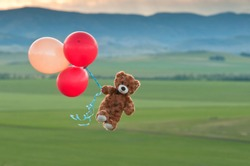 Teddy bear flying to the sky with a big yellow and red balloons.  A bear fly over the fields.  Pooh balloon travel. Aerial travel. Coronavirus.