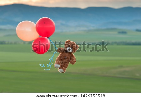 Photo of  Teddy bear flying to the sky with a big yellow and red balloons.  A bear fly over the fields.  Pooh balloon travel. Aerial travel. Coronavirus.