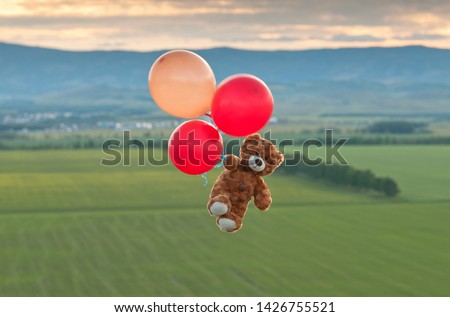 Photo of  Teddy bear flying to the sky with a big yellow and red balloons.  A bear fly over the fields.  Pooh balloon travel. Aerial travel.