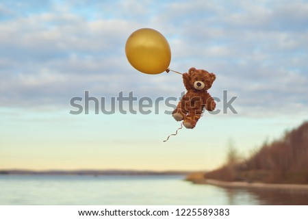 Photo of  Teddy bear flying to the sky with a big yellow ball.  A bear fly over the lake. Winnie Pooh flying with balloon.  Pooh balloon travel. Aerial travel. Happy toys flies.UFO. Winnie the Pooh.