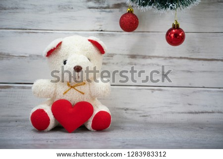 Teddy bear holding a heart-shaped pillow with plank wood board background  #1283983312