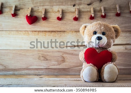 Teddy bear holding a heart-shaped pillow with plank wood board background #350896985