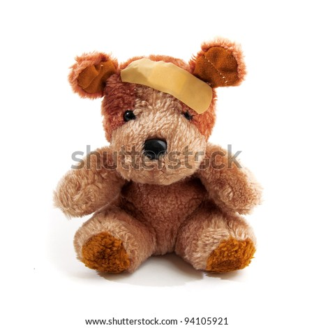 Teddy bear hurt with plaster on his head over a white background