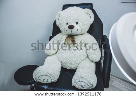 Teddy bear in cosmetic chair, lamp magnifier for beautician , beautician workplace, black chair beauticia #1392511178
