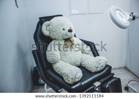 Teddy bear in cosmetic chair, lamp magnifier for beautician , beautician workplace, black chair beauticia #1392511184
