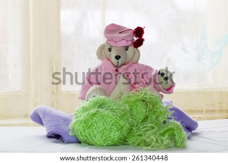 teddy bear in pink blouse and pink beret with red pom-poms on the background of bright windows, a bright sunny day and a festive spring mood. Tangles and threads,
