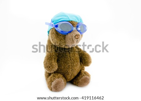 Teddy bear in swimming cap with glass on white background