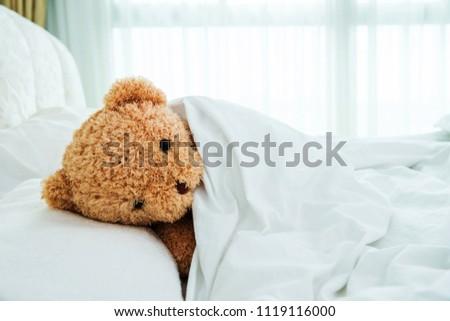 Teddy Bear lying in comfort bed #1119116000