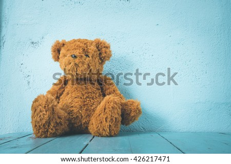 Teddy bear on a table have blue background, alone   #426217471