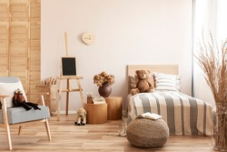 Teddy bear on single wooden bed in natural kid's bedroom