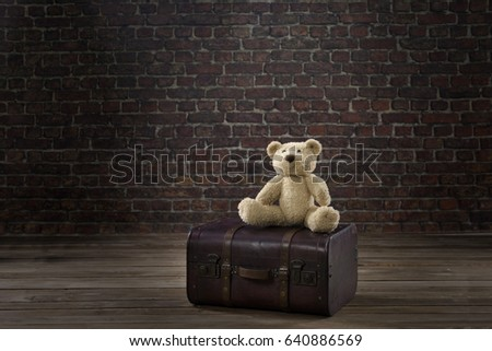 teddy bear on vintage suitcase