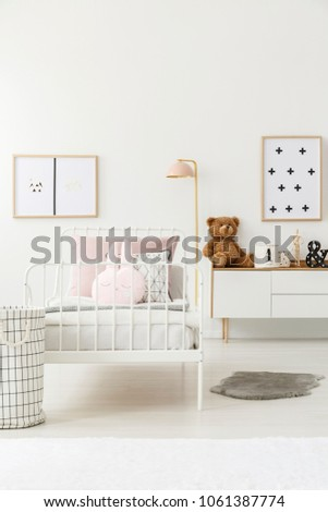Teddy bear on white cupboard next to a metal bed in kid's bedroom interior with posters
