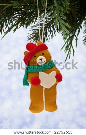 Teddy bear ornament hanging from a tree on snowflake background - stock photo