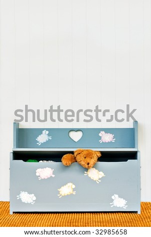 Teddy bear poking his head out of a child's toy box.