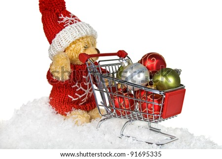 teddy bear pushing a shopping cart filled with ornaments