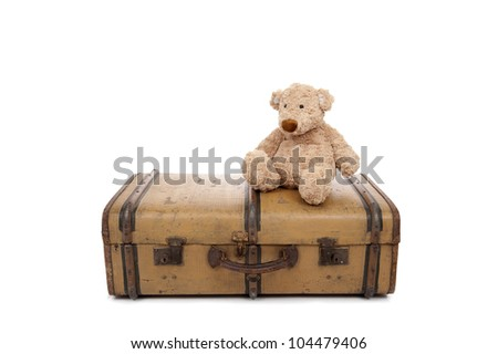 Teddy bear seated on an old vintage suitcase