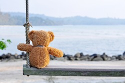Teddy Bear sitting on the wooden swing with blue sea and sky background. Concept about loneliness.