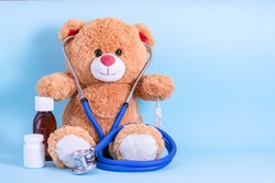 Teddy bear, stethoscope, thermometer, pills and cough syrup on blue background with space to copy; fun Pediatrics concept; children's medicine