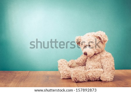 Stock Photo Teddy Bear toy alone on wood in front mint green background
