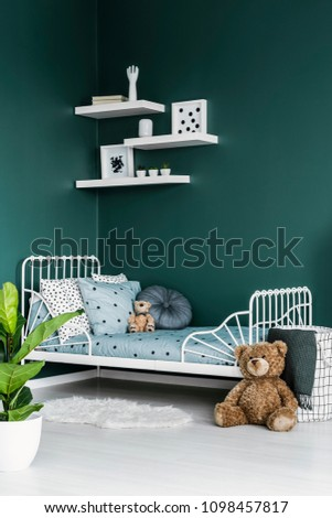 Teddy bear toy by a white twin bed in a dark green room interior for a child with white decor and a plant