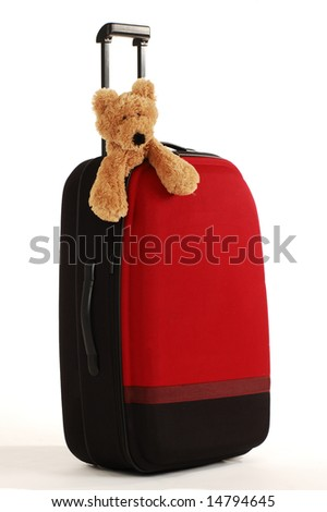 teddy bear toy on a red suitcase with long handle - stock photo