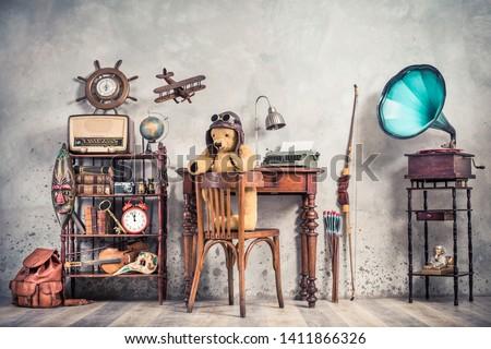 Teddy Bear toy on chair, typewriter, vintage gramophone, old books, radio, globe, binoculars, carnival mask, camera, fiddle on shelf, steering wheel, plane, travel backpack, bow. Retro style photo Foto stock ©