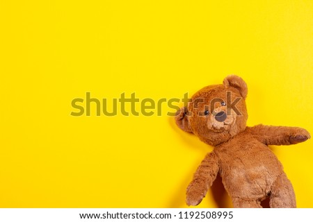 Teddy bear toy on yellow background. Top view