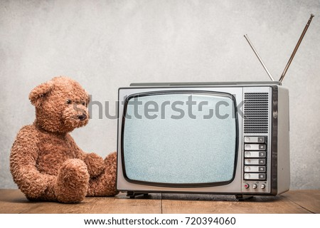Teddy Bear toy watching retro old monochrome TV set receiver on table front textured concrete wall background. Television broadcasting concept