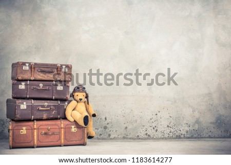 Teddy Bear toy with leather aviator's hat and goggles sitting on retro old aged classic travel suitcases circa 1940s. Travel luggage concept. Vintage instagram style filtered photo