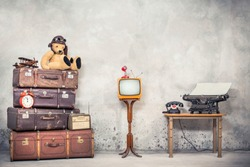 Teddy Bear toy with leather aviator's hat and goggles sitting on retro old  travel suitcases, wooden plane, alarm clock, TV, mic, telephone and typewriter. Loft storage. Vintage style filtered photo
