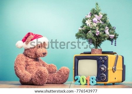 Teddy Bear toy with Santa hat, Christmas tree, retro TV and New Year 2018 date front mint green background. Holidays greeting card concept. Vintage old style filtered photo