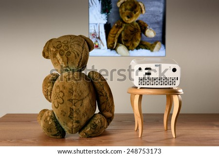 Teddy Bear watching his photos with a mini projector. The transfer of the image is wireless.