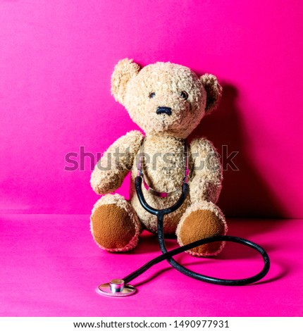 teddy bear with a stethoscope for checking health and injury after mishap at the hospital over pink copy space background  #1490977931