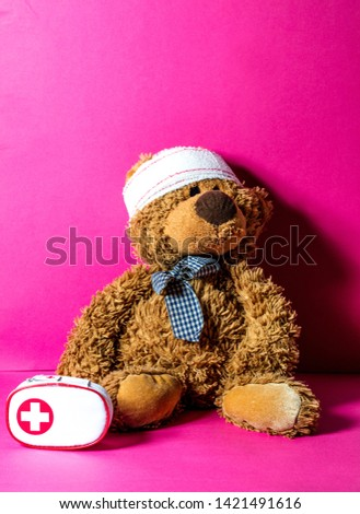 Teddy bear with bandage at the head and first aid kit for mishap concept of healthcare education over pink background #1421491616